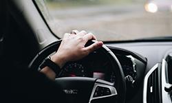 Frau die Auto fährt und eine Hand am Lenkrad hat (das andere bestimmt am Radio und macht Katy Perry oder Cardi B an)